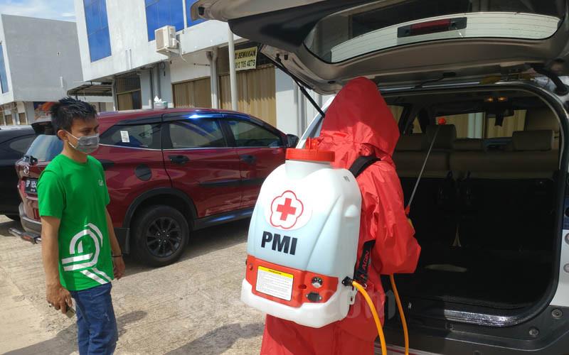Petugas dari PMI Kota Batam ketik melakukan penyemprotan cairan desinfektan ke kendaraan mitra Grab Kota Batam pada Jumat (3/4/2020). - Bisnis/Bobi Bani.