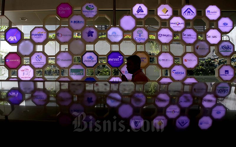 Karyawan berkomunikasi didekat logo beberapa perusahaan asuransi di kantor Asosiasi Asuransi Jiwa Indonesia (AAJI) di Jakarta, Selasa (15/1/2020). Bisnis - Nurul Hidayat
