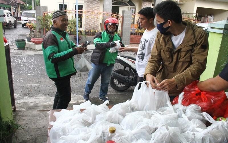 Relawan memberikan nasi bungkus pada seorang pengemudi ojek daring di Dapur Umum COVID-19, di Malang, Jawa Timur, Senin (6/4/2020). Dapur umum tersebut sengaja didirikan untuk meringankan beban para pengemudi ojek daring serta pekerja lapangan yang terpaksa bekerja di luar rumah di tengah pandemi Covid-19, dengan menyediakan 100 bungkus makanan gratis setiap hari. - Antara/Ari Bowo Sucipto