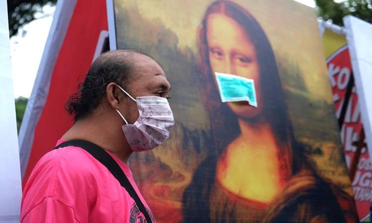 Pengunjung memakai masker saat mengamati karya lukis dan karikatur pada pameran bertajuk Masker di Solo, Jawa Tengah, Minggu (8/3/2020). Pameran tersebut sebagai bentuk ekspresi seniman untuk mengajak masyarakat turut mendoakan dan memberi dukungan bagi pasien yang telah dinyatakan positif terjangkit virus corona serta menghormati hak pribadinya. ANTARA FOTO - Maulana Surya
