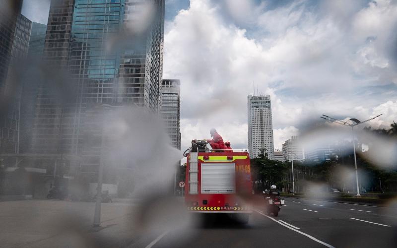 nPetugas pemadam kebakaran menyemprotkan cairan disinfektan di Jalan Jenderal Sudirman, Jakarta, Jumat (3/4/2020). Penyemprotan tersebut dilakukan rutin setiap hari yang dimulai dari kawasan Medan Merdeka Barat hingga Senayan dan menghabiskan 14 ribu liter cairan disinfektan guna menekan penyebaran virus corona (COVID-19). - ANTARA FOTO/Dhemas Reviyanto