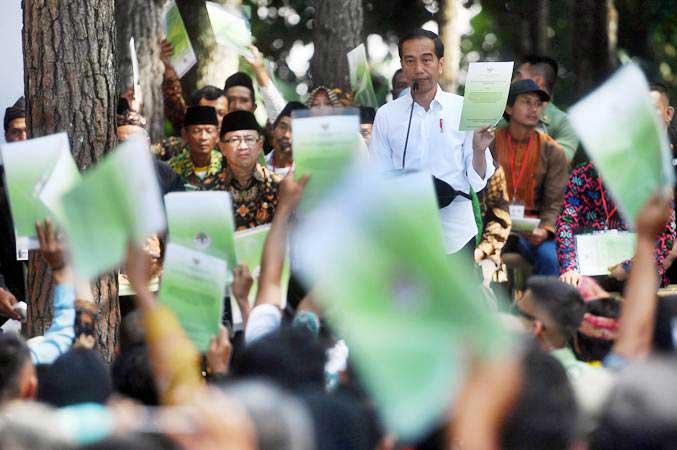 Presiden Joko Widodo menunjukkan Surat Keputusan tentang Pengelolaan Hutan Sosial saat berpidato di Wana Wisata Pokland Haurwangi, Cianjur, Jumat (8/2/2019). - ANTARA/Akbar Nugroho Gumay