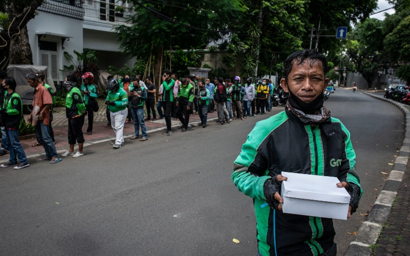 Pengemudi ojek daring menunjukkan nasi kotak yang didapatkannya di kawasan Menteng, Jakarta, Jumat (3/4/2020). Pembagian makanan gratis tersebut merupakan sebagai bentuk kepedulian terhadap sesama di tengah-tengah pandemi COVID-19. - ANTARA FOTO/Aprillio Akbar