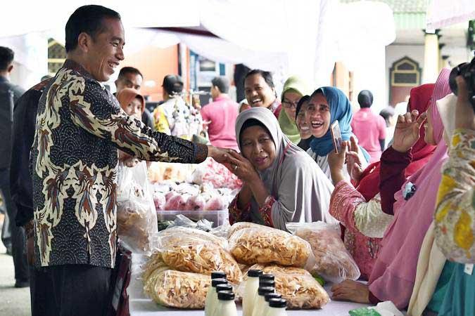 Presiden Joko Widodo (kiri) berjabat tangan dengan penerima Bantuan Sosial Program Keluarga Harapan (PKH) Tahun 2019 di Sukmajaya, Depok, Jawa Barat, Selasa (12/2/2019). - ANTARA FOTO/Puspa Perwitasari