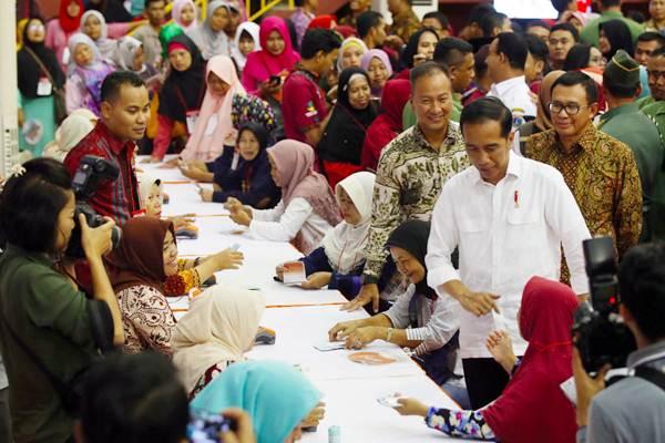 Presiden Joko Widodo (kedua kanan) didampingi Menteri Sosial Agus Gumilang Kartasasmita (ketiga kanan) dan Direktur Utama BNI Achmad Baiquni (kanan) meninjau penyaluran Dana Bantuan Sosial Non Tunai Program Keluarga Harapan (PKH) kepada Keluarga Penerima Manfaat (KPM), di Jakarta, Kamis (10/1/2019). - Bisnis/Abdullah Azzam