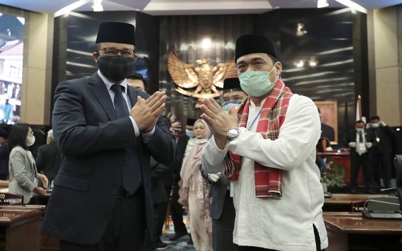 Gubernur DKI Jakarta Anies Baswedan (kiri) didampingi Wakil Gubernur DKI Jakarta terpilih Ahmad Riza Patria (kanan) memberi salam usai pemilihan di Gedung DPRD DKI Jakarta di Jakarta, Senin (6/4/2020). - Antara