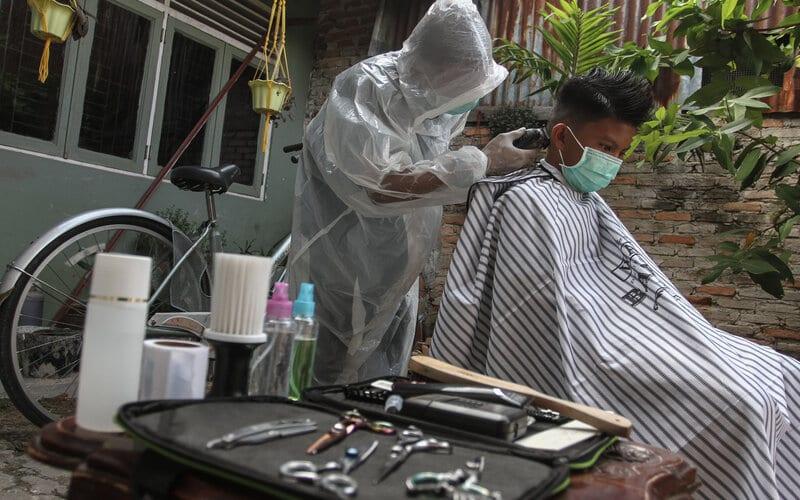 Seorang tukang cukur menggunakan Alat Pelindung Diri (APD) ketika memotong rambut di halaman rumah pelanggan, di Pekanbaru, Riau, Kamis (9/4/2020). Sepinya pengunjung yang datang ke barbershop membuat pelaku usaha potong rambut menerima jasa panggilan cukur ke rumah dengan menggunakan pakaian pelindung untuk pencegahan penularan virus Corona (Covid-19). - Antara/Rony Muharrman
