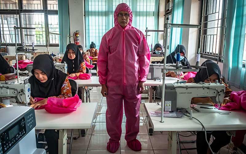 Seorang peserta pelatihan Balai Latihan Kerja (BLK) mengenakan alat pelindung diri (APD) yang diproduksi sesuai dengan standar keamanan Gugus Tugas Penanganan COVID-19 di BLK Dinas Tenaga Kerja Kota Semarang, Jawa Tengah, Jumat (27/3/2020). Pemkot Semarang menargetkan dapat memproduksi  100 unit baju pelindung tenaga medis per hari dengan total target 5.000 unit untuk didistribusikan secara gratis ke sejumlah rumah sakit yang menangani kasus virus Corona (COVID-19) di Kota Semarang. ANTARA FOTO - Aji Styawan