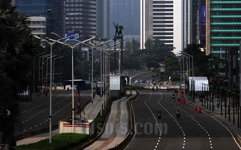Kendaraan melintas di Jalan Jendral Sudirman  yang lenggang di Jakarta,Jumat (10/4).  Dalam rangka percepatan penganganan COVID-19, Pemerintah Provinsi DKI Jakarta menerapkan Penerapan Sosial Berskala Besar (PSBB) yang mulai berlaku hari ini hingga 14 hari kedepan. nBisnis - Dedi Gunawan