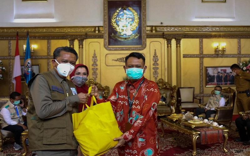 Pemimpin PT Pegadaian Wilayah VI Alim Sutiono menyerahkan paket bantuan sembako kepada Gubernur Sulawesi Selatan Nurdin Abdullah, Senin (13/4/2020) - Istimewa