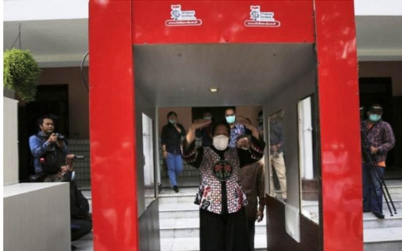 Wali Kota Surabaya Tri Rismaharini saat mencoba alat disinfektan baru penangkal Covid-19 berupa bilik yang diberi nama 'Bilik Disinfektan Trisakti' di halaman Rumah Dinas Wali Kota Surabaya, Sabtu (21/3/2020). - ANTARA Jatim