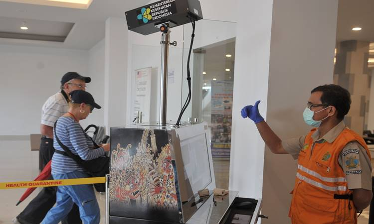 Petugas memantau suhu tubuh penumpang menggunakan alat pemindai suhu tubuh yang dipasang di Terminal Penumpang Kapal Pesiar Pelabuhan Benoa, Bali, Minggu (8/3/2020). ANTARA FOTO - Fikri Yusuf