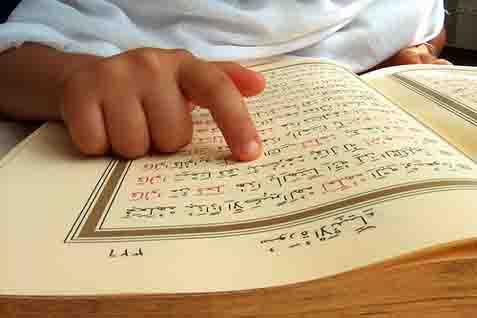 Ilustrasi: Seorang anak yang sedang membaca Alquran