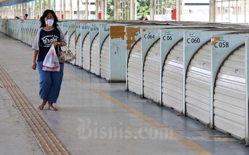Warga berjalan melintasi Pasar Tanah Abang yang tutup di Jakarta, Senin (6/4/2020). Pemerintah Provinsi DKI Jakarta memperpanjang penutupan sementara Pasar Tanah Abang hingga Senin (19/4) sebagai bentuk pencegahan penyebaran COVID-19. Bisnis - Eusebio Chrysnamurti