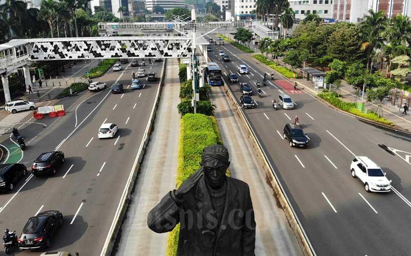 Kendaraan melintas di Jalan Sudirman saat diberlakukan Pembatasan Sosial Berskala Besar (PSBB) di Jakarta, Senin (13/4/2020). Bisnis - Himawan L Nugraha