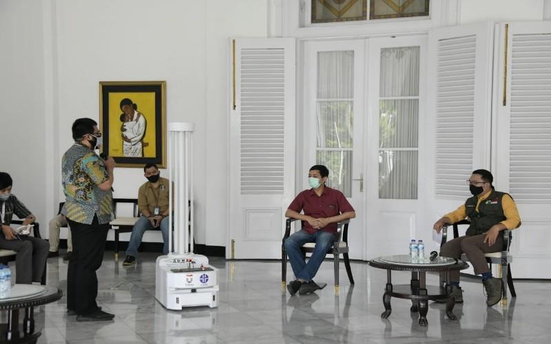 Tim Telkom University memperlihatkan kemampuan robot disinfektan kepada Gubernur Jawa Barat Ridwan Kamil, di Gedung Pakuan Bandung, Sabtu (18/4 - 2020).