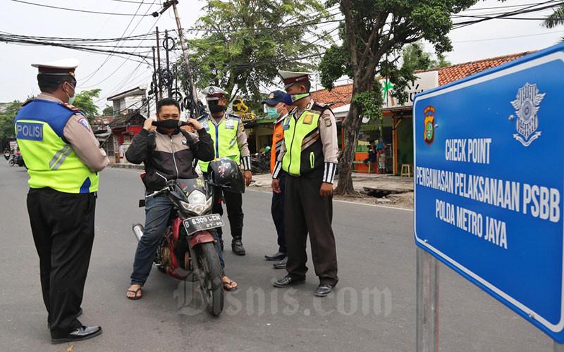 Ilustrasi - Petugas gabungan melaksanakan pengawasan dalam Penerapan Sosial Berskala Besar (PSBB) di Jalan Ciledug Raya, Jakarta, Jumat (10/4/2020). Kegiatan pelaksanaan pengawasan PSBB itu dilakukan untuk mengingatkan kewajiban warga untuk memakai masker dan aturan penumpang dalam satu kendaraan. Bisnis - Eusebio Chrysnamurti