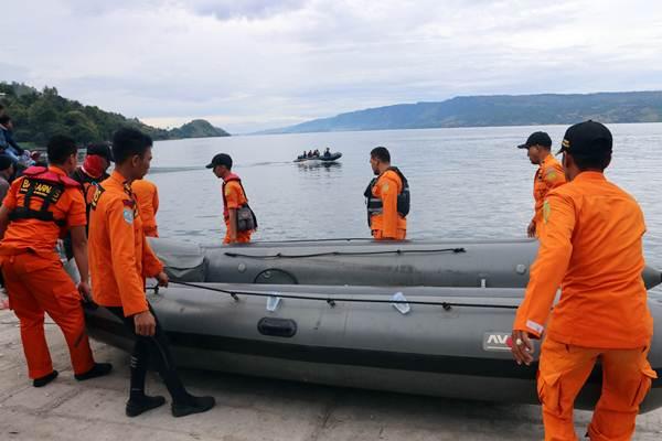 Personel Basarnas mengangkat perahu karet saat akan melakukan pencarian korban KM Sinar Bangun yang tenggelam di Danau Toba, Simalungun, Sumatra Utara, Rabu (20/6/2018). - ANTARA/Irsan Mulyadi