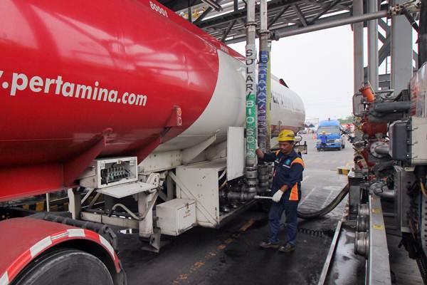 Petugas mengisi bahan bakar minyak (BBM) ke truk tangki di Terminal Bahan Bakar Minyak (TBBM) Tanjung Perak, Surabaya, Jawa Timur, Kamis (20/12/2018). Pengangkutan BBM dikecualikan dalam PSBB. - Antara/Didik Suhartono