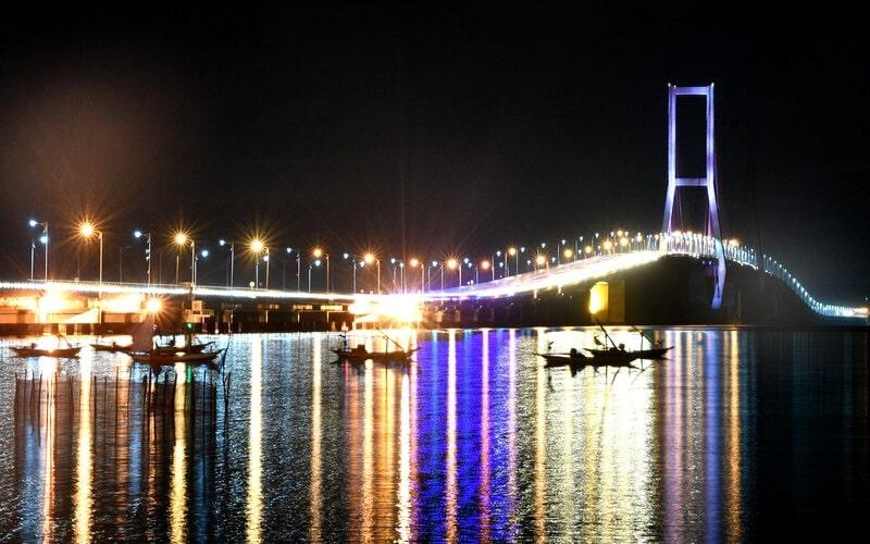 Sejumlah perahu nelayan ditambatkan di sisi timur Jembatan Suramadu di Surabaya, Jawa Timur, Sabtu (18/4/2020). Akibat pandemi virus Corona (Covid-19), suasana di kawasan itu sepi pengunjung. - Antara/Zabur Karuru