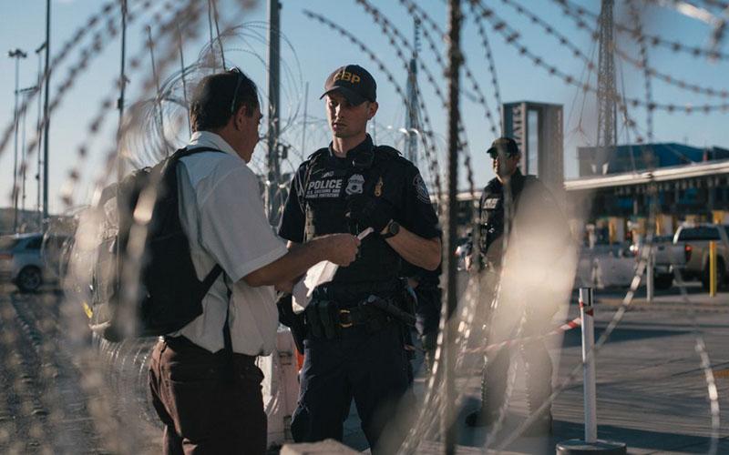 Seorang petugas Bea Cukai dan Perlindungan Perbatasan AS berbicara dengan seorang pria di pelabuhan masuk San Ysidro di Tijuana, Meksiko, pada 26 November 2018./Bloomberg - Luis Antonio Rojas