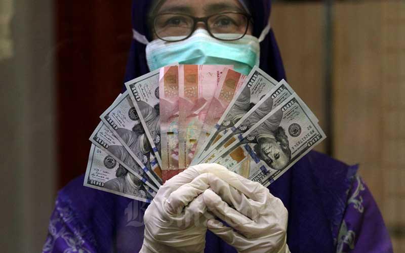 Karyawati menunjukan mata uang Rupiah dan Dolar AS di salah satu gerai penukaran mata uang asing di Jakarta, Kamis (2/4/2020). - Bisnis/Arief Hermawan P