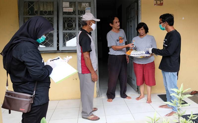 Ilustrasi - Petugas Jaring Pengaman Sosial (JPS) swadaya tingkat desa memberikan bantuan sembako kepada warga terdampak COVID-19 di Perumahan Candi Asri, Kedu, Temanggung, Jawa Tengah, Rabu (8/4/2020). Warga setempat secara swadaya melakukan iuran yang hasilnya disumbangkan kepada warga terdampak COVID-19 berupa sembako dan hand sanitizer. ANTARA FOTO - Anis Efizudin