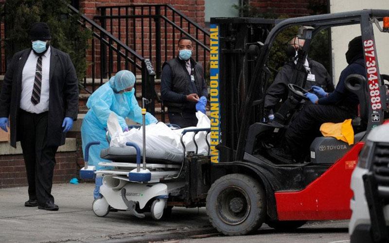 Pekerja bersiap untuk memindahkan jenazah ke dalam trailer di luar Rumah Sakit Pusat Brooklyn di tengah pandemi virus corona di New York, Amerika Serikat, Senin (30/3/2020). - Antara-Reuters