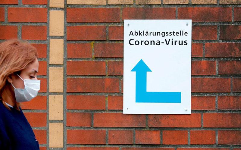 Seorang perempuan mengenakan masker berjalan melewati papan petunjuk yang memandu orang ke pintu masuk stasiun penguji korona di sebuah rumah sakit di Berlin, Jerman. - Bloomberg
