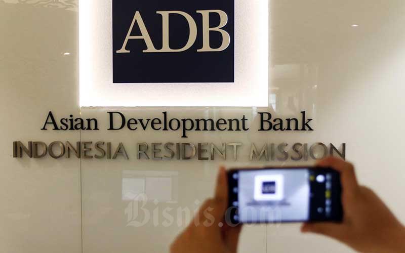 Karyawan memotret logo Asian Development Bank Indonesia di Jakarta, Rabu (8/4/2020). Bisnis - Eusebio Chrysnamurti