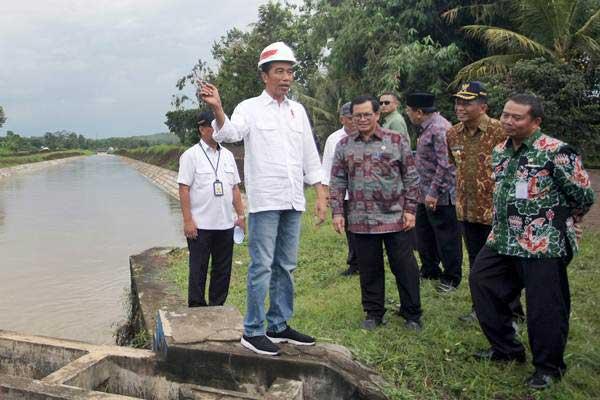 Presiden Joko Widodo (kiri) meninjau salah satu lokasi rehabilitasi irigasi di Sungai Lodoyo, Blitar, Jawa Timur, Kamis (3/1/2019). - ANTARA/Irfan Anshori