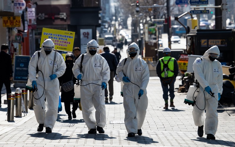 Tentara Korea Selatan mengenakan Alat Pelindung Diri (APD) sembari menyemprotkan disinfektan di jalanan Seoul, Korea Selatan, Kamis (5/3/2020). - Bloomberg/SeongJoon Cho
