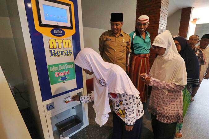 Warga antre menggunakan mesin Anjungan Tunai Mandiri (ATM) Beras di masjid Al Khalid di Kelurahan Semampir, Kota Kediri, Jawa Timur, Senin (18/3/2019). - ANTARA/Prasetia Fauzani