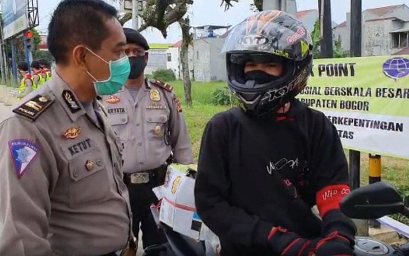 Petugas kepolisian memberikan arahan kepada pengendara motor mengenai penerapan Pembatasan Sosial Berskala Besar (PSBB) di salah satu check point di Kabupaten Bogor, Jawa Barat. - Antara