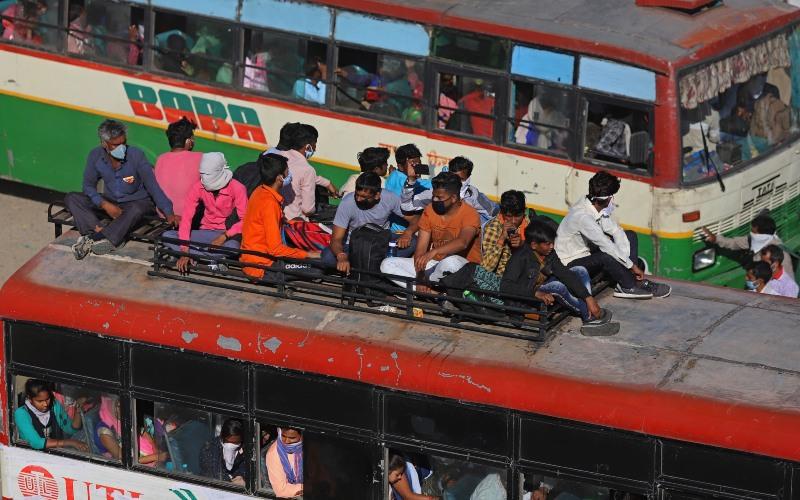 Para pekerja migran dan keluarganya menaiki bus di tengah lockdown yang diberlakukan pemerintah di New Delhi, India, pada Sabtu (28/3/2020)./Bloomberg - Anindito Mukherjee