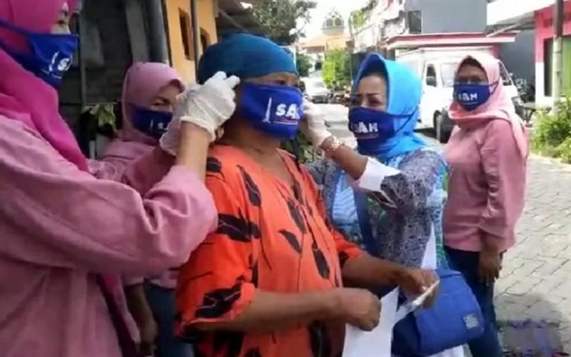 Ketua Pengurus Wilayah Ikatan Notaris Indonesia (INI) Jawa Timur Siti Anggreanie Hapsari (SAH) memakaikan masker kepada warga saat baksos di Lakarsantri Kota Surabaya, Minggu (26/4/2020). - Antara