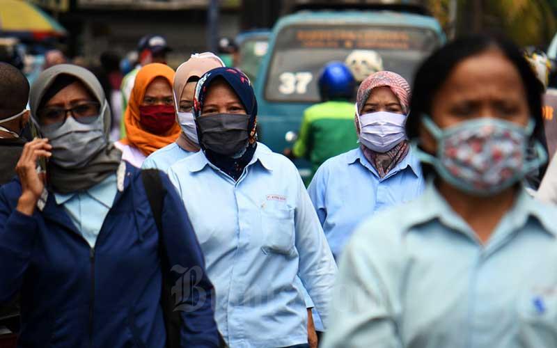 Pekerja pabrik pulang seusai bekerja di salah satu pabrik makanan di Jakarta, Sabtu (11/4/2020). - Bisnis/Abdurachman