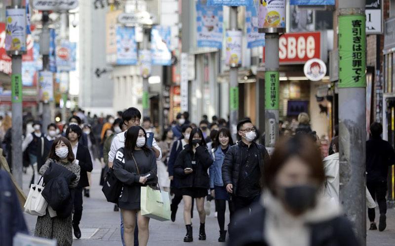 Para pejalan kaki di Shibuya, Tokyo, Jepang, pada 26 Maret 2020 mengenakan masker untuk mencegah penyebaran virus corona jens Covid-19./Bloomberg - Kiyoshi Ota/msl