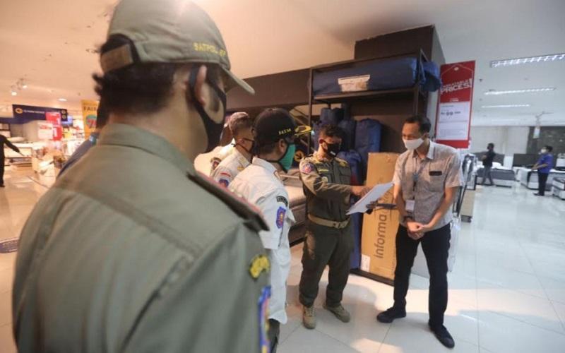 Tim Satpol PP saat mendatangi toko yang masih beroperasi saat PSBB - Bisnis/Dea Andriyawan