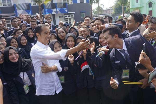 Presiden Joko Widodo (tengah) berswafoto dan membuat video story (vlog) bersama para mahasiswa usai meresmikan tiga unit rusunawa di halaman kampus STKIP Tulungagung, Jawa Timur, Jumat (4/1/2019). - ANTARA/Destyan Sujarwoko