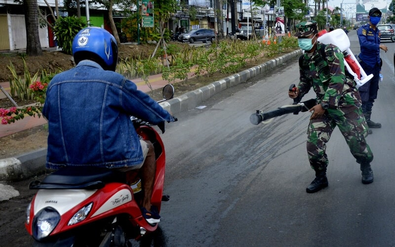 Petugas melakukan penyemprotan disinfektan dan pemeriksaan kendaraan yang memasuki wilayah Gowa saat uji coba penerapan Pembatasan Sosial Berskala Besar (PSBB) di Kabupaten Gowa, Sulawesi Selatan, Sabtu (25/4/2020). Pemerintah Kabupaten Gowa melakukan uji coba penerapan PSBB selama lima hari agar penerapan PSBB yang akan dilaksanakan pada (29/4/2020) dapat berjalan efektif dalam percepatan penanganan Covid-19. - Antara/Abriawan Abhe