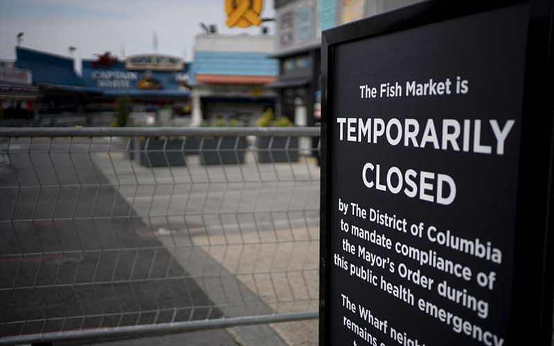 Pengumuman penutupan sementara pasar ikan di The Wharf, Washington, DC, Amerika Serikat, Selasa (7/4/2020). Amerika Serikat masih menjadi negara dengan kasus Covid-19 terbesar. Hingga Rabu (8/4/2020), kasus positif Covid-19 di Negeri Paman Sam itu telah mencapai 396.416 kasus. Bloomberg - Andrew Harrer
