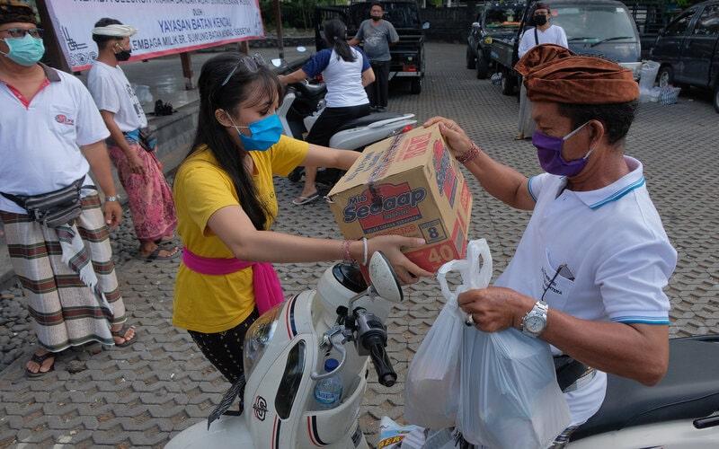 Relawan menyerahkan sumbangan barang kebutuhan pokok kepada warga sebagai bantuan pangan akibat wabah COVID-19 di Lingkungan Suwung Batan Kendal Denpasar, Bali, Minggu (12/4/2020). Bantuan sembako secara swadaya tersebut untuk meringankan beban perekonomian warga setempat yang sebagian besar bekerja di sektor pariwisata yang kini anjlok akibat wabah COVID-19 atau Virus Corona. - Antara/Nyoman Hendra Wibowo