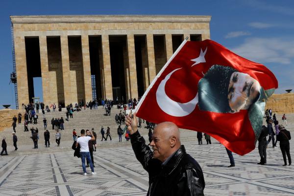 Seorang pria mengibarkan bendera Turki dengan potret Mustafa Kemal Ataturk di depan Anitkabir, tempat peristirahatan Ataturk, di Ankara, Turki, Selasa (2/4/2019). - Reuters/Umit Bektas