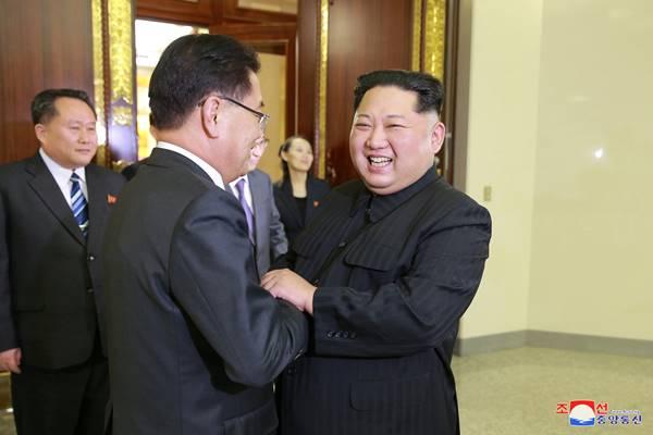 Pemimpin Korea Utara Kim Jong-un menyambut seorang anggota delegasi khusus Presiden Korea Selatan saat makan malam, 6 Maret 2018. Foto dirilis Kantor Berita Korea Utara. - Reuters