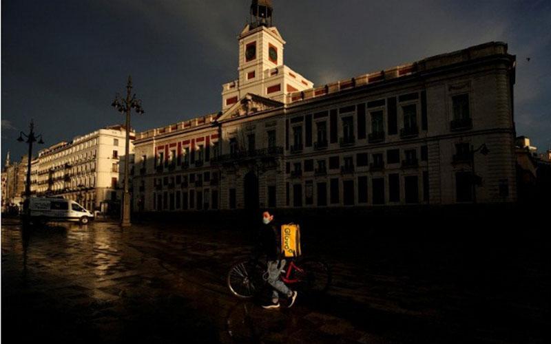 Kurir pengantar makanan Glovo memakai masker saat berjalan melewati lapangan Puerta del Sol yang kosong akibat penerapan karantina ditengah wabah virus corona Covid-19 di Madrid, Spanyol, Minggu (19/4/2020)./Antara - Reuters