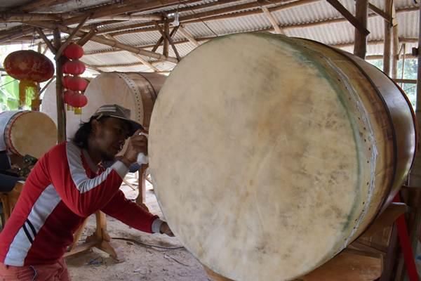Perajin menyelesaikan pembuatan bedug di tempat kerajinan bedug, Magetan, Jawa Timur, Rabu (7/6). Tempat kerajinan bedug tersebut dalam sebulan bisa menyelesaikan pembuatan rata-rata 15 hingga 30 unit bedug yang dijual dengan harga Rp3 juta hingga ratusan juta rupiah. ANTARA FOTO - Siswowidodo