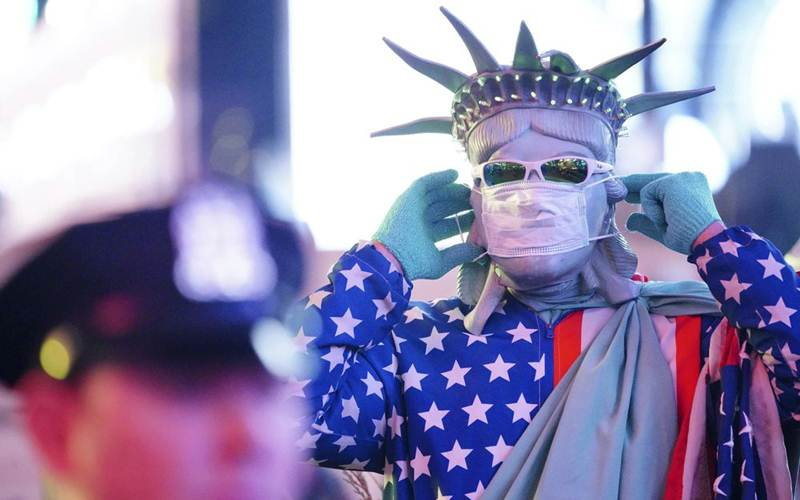 Seorang pria mengenakan masker di Times Square, New York./Bloomberg-John Nacion/STAR MAX - IPx via AP Photo