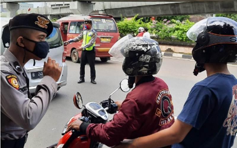 Petugas Satlantas Polres Metro Jakarta Selatan menegur pengendara sepeda motor yang tidak menggunakan masker saat melintas di check point Pasar Jumat, Jakarta Selatan, Sabtu (11/4/2020). - ANTARA/Laily Rahmawaty