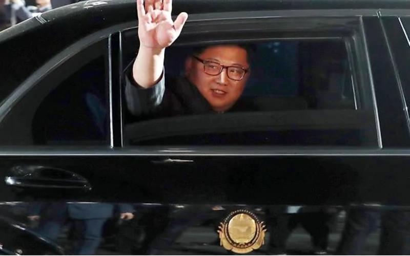 Pemimpin Korea Utara (Korut) Kim Jong-un melambaikan tangan dari dalam mobil yang ditumpanginya. - Istimewa